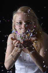 Young woman blowing confetti - BFRF000470