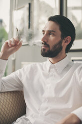 Portrait of young man smoking cigarillo - MFF001148