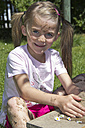 Portrait of little girl playing with sand in the garden - YFF000198