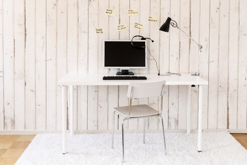 Home office with personal computer, headset and sticky notes on the wall - DRF000872
