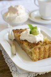 Piece of gooseberry almond tart with cream on plate - HAWF000373