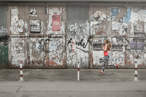 Germany, Lower Saxony, Hanover, young female jogger running in front of an decayed building - GC000028