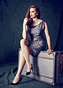 Portrait of well dressed woman sitting on an old suitcase - KDF000007