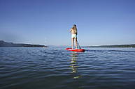 Germany, Bavaria, young woman standing on stand up paddle board at Lake Starnberg, back view - FAF000019