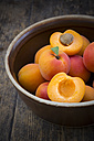 Bowl of sliced and whole apricots on wood - LVF001532