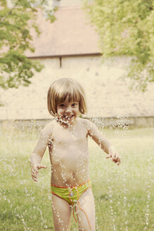 Portrait of little girl having fun with lawn sprinkler in the garten - LVF001579