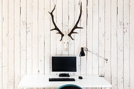 Home office with personal computer and deer antler hanging on wooden wall - DRF000940