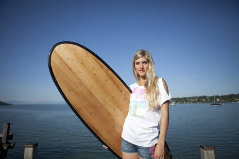 Portrait of young woman with surfboard in front of a lake - FAF000024