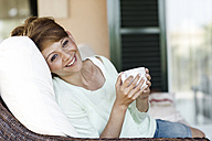 Smiling brunette woman holding cup - GDF000350