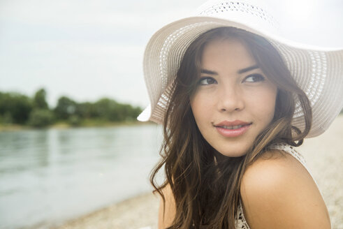 Portrait of young woman on the beach wearing white summer hat - UUF001202