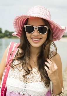 Portrait of smiling young woman wearing sunglasses and pink hat on the beach - UUF001207