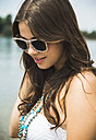 Portrait of smiling young woman wearing sunglasses - UUF001216