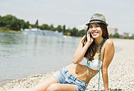 Portrait of smiling young woman telephoning on the beach - UUF001227