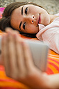 Portrait of smiling young woman lying on beach towel taking a selfie - UUF001298