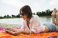 Portrait of young woman lying on beach towel using digital tablet - UUF001270