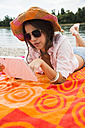 Portrait of young woman with summer hat and sun glasses using digital tablet - UUF001358