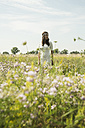 Portrait of young woman standing on flower meadow - UUF001239