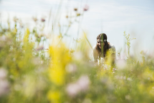 Portrait of smiling young woman standing on flower meadow - UUF001242