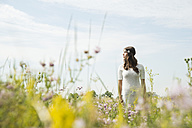 Young woman standing on flower meadow - UUF001243