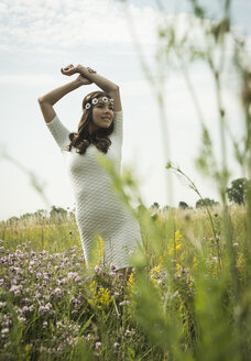 Portrait of young woman relaxing on flower meadow - UUF001247