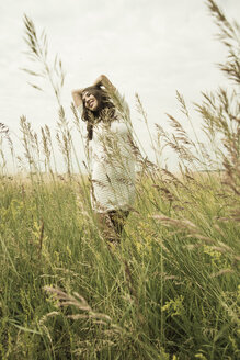 Young smiling woman standing on flower meadow - UUF001260