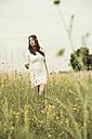 Portrait of young woman walking on flower meadow - UUF001261