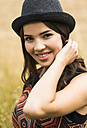 Portrait of smiling young woman wearing a black hat - UUF001308