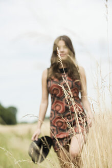 Young woman walking on a meadow - UUF001315