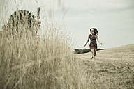 Young woman running on a harvested meadow - UUF001320