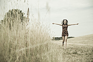 Young womanwith outstretched arms running on a harvested meadow - UUF001321