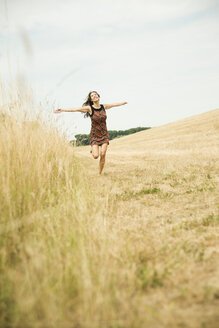 Young woman running on a harvested meadow - UUF001323