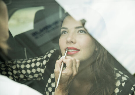 Female visagiste applying lipstick on young woman's lips - UUF001328