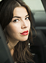 Portrait of young woman with red lips sitting in car - UUF001330