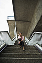 Young woman sitting on staircase waiting - UUF001347
