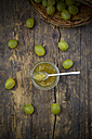 Jar of gooseberry jam and organic gooseberries on dark wood, elevated view - LVF001574