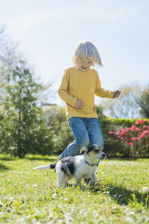 Boy playing with Jack Russel Terrier puppy in garden - MJF001302