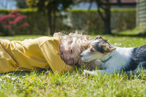 Boy playing with Jack Russel Terrier puppy in garden - MJF001305