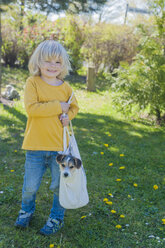 Boy carrying Jack Russel Terrier puppy in bag - MJF001325