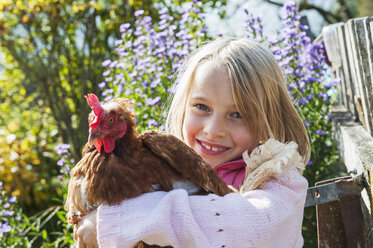 Happy girl hugging hen - HHF004840