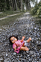 Austria, Linz, doll lying on forest track - EJW000412