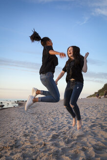 Germany, Ruegen, Two young female friends jumping at the beach - OJF000051