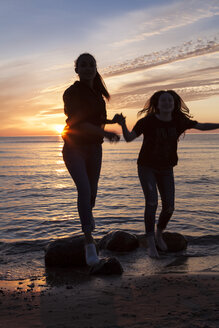 Germany, Ruegen, Two young female friends on the beach at sunset - OJF000057