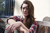 Relaxed young woman sitting outdoors - FEXF000103