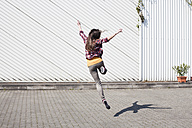 Exuberant young woman jumping outdoors - FEXF000107