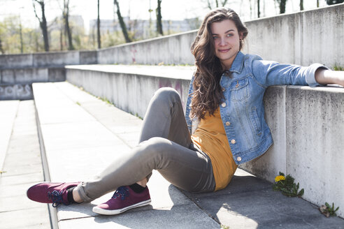 Relaxed young woman sitting outdoors - FEXF000116