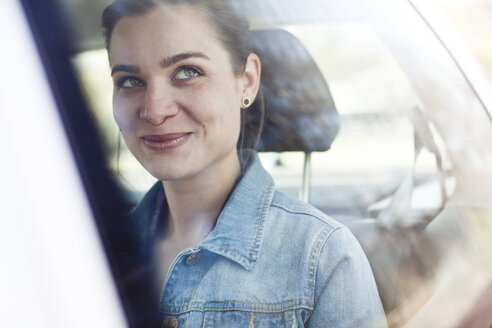 Smiling young woman on back seat of a car - FEXF000094