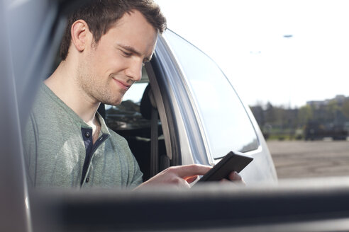 Young man using cell phone in car - FEXF000124