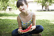 Girl with slice of watermelon licking lips - LVF001677