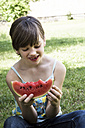 Smiling girl eating slice of watermelon in the garden - LVF001676