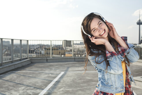 Germany, North Rhine-Westphalia, Cologne, portrait of laughing young woman listening music with headphones - FEXF000139